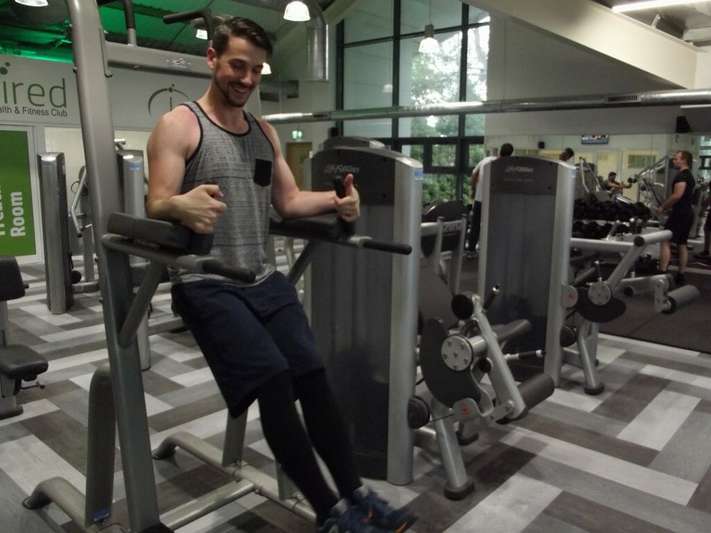 Individual performing leg raises on gym equipment - Gym at Cambridge Innovation Parks